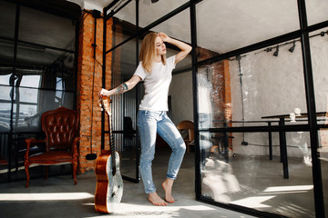 Portrait of the stylish young woman of the blonde in a white t-shirt and jeans in an interior in style the loft. The girl with a guitar.