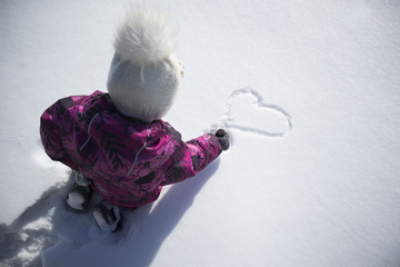 child on the street draws on the snow heart. Winter, love, friendship, concept.