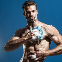 Spa and beauty, relax and hygiene, healthcare - handsome man washing with sponge in shower. Athletic, handsome guy muscular body soaping himself in shower. Man receives relaxing shower after hard day.