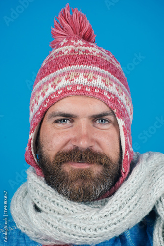 dedb631f7b9 Men winter fashion. Handsome trendy man wearing knit hat and scarf.  Portrait of smiling bearded man with scarf and hat on blue background.