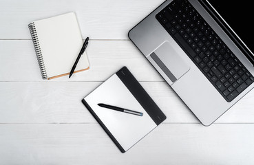 Open laptop computer, blank empty notebook and graphic tablet on white wooden table, free space. Top view, flat lay, copy space for text. Business concept