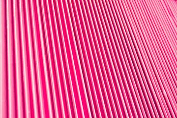 Abstract background of vertical relief metal ribs covered with glamorous pink color.