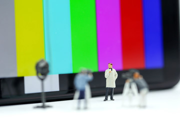 Miniature people : journalists , cameraman ,Videographer at work shooting with colorbar tv background.