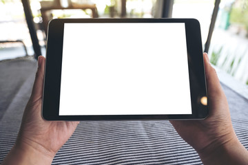 Mockup image of hands holding black tablet pc with blank white desktop screen on table with blur background in cafe