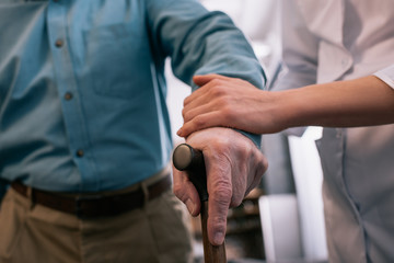 Close-up view of cane in hand of senior man supported by doctor