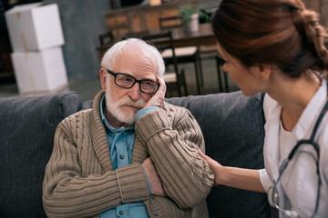 Depressed senior man looking at female doctor