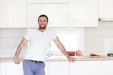 Handsome man cooking at home in kitchen