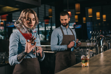 female and male bartenders working at bar