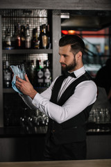 side view of handsome bartender cleaning glass with rag in evening