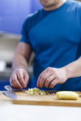 man cuts vegetables on a wooden lumber in the kitchen