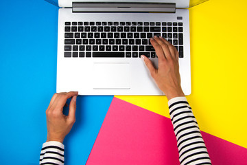 Woman hands using laptop on colorful background