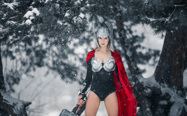 Woman in image of Germanic-Scandinavian God of thunder and storm stands with hammer in her hand. Cosplay.