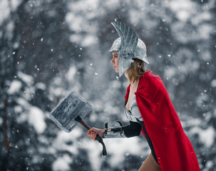 Woman in image of Germanic-Scandinavian God of thunder and storm goes with hammer in her hand. Cosplay.