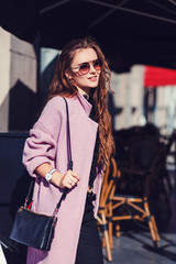 Portrait of cute girl with long curly hair and smiling in city