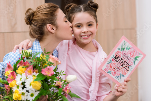mother kissing her daughter with mothers day greeting card