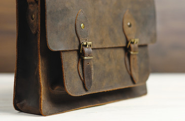 Bag briefcase for businessman men, leather brown bag on a wooden background. Men's fashion, accessory, business background. Selective focus.