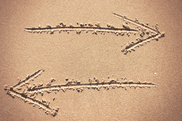 Two arrow signs drawing in sand background