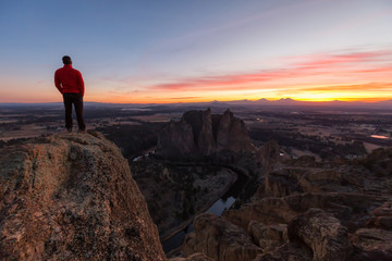 Man standing on top of a mountain is enjoying a beautiful landscape during a colorful and vibrant sunset. Taken at Smith Rock, Oregon, North America.