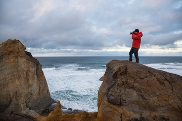 Photographer taking pictures of Kape Kiwanda in Oregon Coast, United States of America
