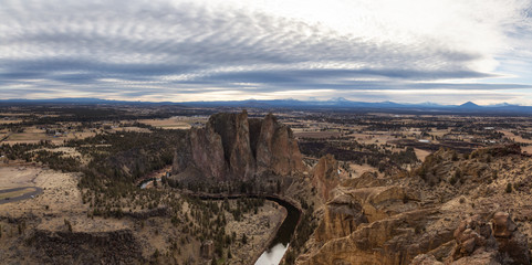 Striking panoramic landscape of the famous location, Smith Rock, during a winter cloudy evening. Taken in Oregon, United States of America.