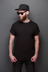 Hipster handsome male model with beard wearing black blank t-shirt with space for your logo or design over gray background