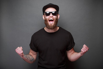 Hipster handsome male model with beard wearing black blank t-shirt with space for your logo or design over gray background Wall mural