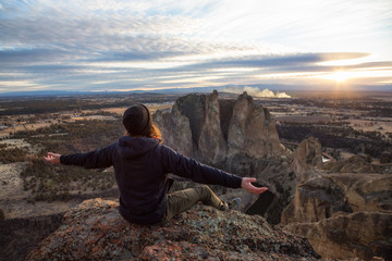 Adventurous man with open arms is enjoying the beautiful sunset from the top of the mountain. Taken in Smith Rock, Oregon, North America.