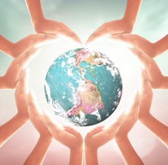 International human solidarity day concept: Heart shape of hands holding earth globe over blurred nature background. Elements of this image furnished by NASA