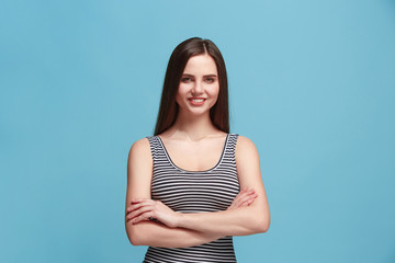 The happy woman standing and smiling against blue background.