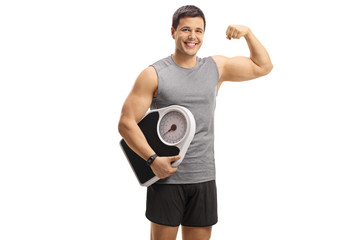 Young guy in sportswear holding a weight scale and flexing his biceps