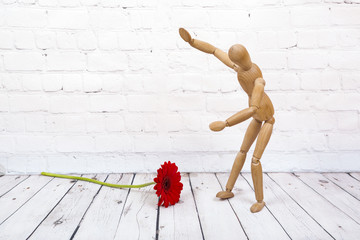 Wooden mannequin with red gerbera flower