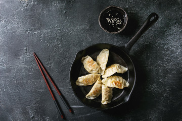 Asian dumplings Gyozas potstickers fried on cast-iron pan, served with chopsticks and bowl of soy sesame sauce over black texture background. Top view, space.