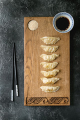 Asian dumplings Gyozas potstickers served with chopsticks and bowl of soy sesame sauce on asian style wooden board over black texture background. Top view, space.