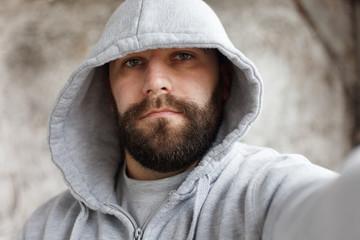 bearded man on a gray background makes a selfi