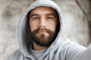 bearded man on a gray background makes a selfi