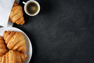 Croissants and coffee on a dark background. Breakfast flat lay.
