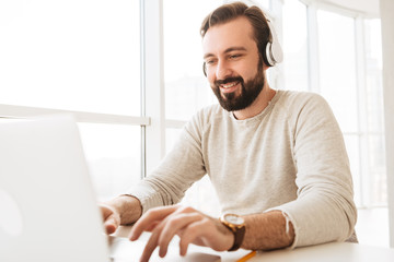 Photo of attractive mature man 30s in casual clothing typing text message or working on laptop, while listening to music via earphones