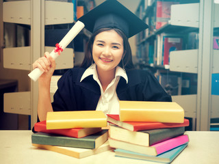 Young asian female student holding book and wearing academic costume in library,education, happiness, graduation and people concept.