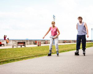 Friends rollerblading together have fun in park.