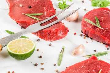 Fresh raw meat. Beef tenderloin, steaks, on a white marble table. With olive oil, spices for cooking - basil, rosemary, coriander, parsley, garlic, lemon, salt, pepper. Copy space