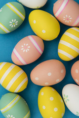 Easter holiday background. Pastel colored decorated easter eggs on a bright blue background