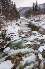 Winter landscape. Mountain river flows from the rocks. Snow and mountain river