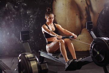 female using rowing machine in gym. Young woman doing cardio workout in fitness club.