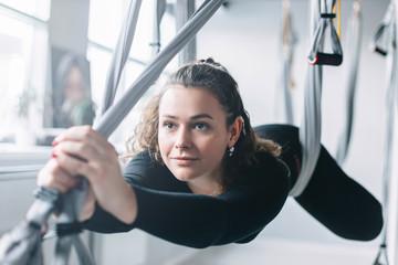 girl stretching on hammocks. yoga.