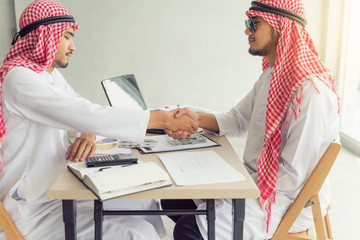 Businessmen arabian handshake each other when business dealing complete