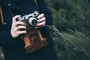 Woman's hands holding retro photo camera and taking photo outdoor. Lifestyle concept with autumn nature on background. Close-up. Tone photo
