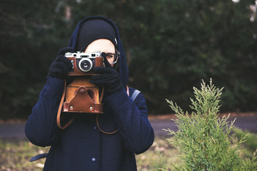 Portrait of young woman holding retro photo camera and taking photo in the park. Lifestyle concept with autumn nature on background. Tone photo