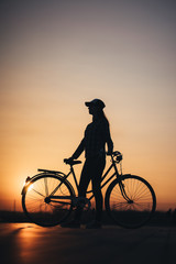 Woman riding a bike in the city during sunset