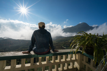 Male tourist sit on balcony seeing mountain landscape with low white clouds under brilliant sky. Ideas for travel and feeling.