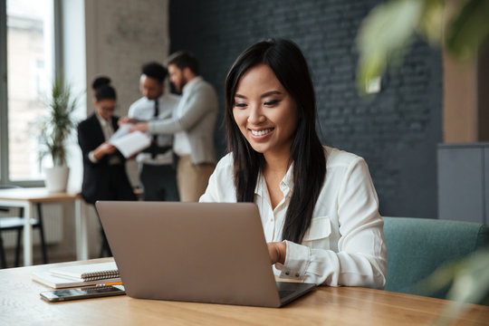 Cheerful young asian business woman using laptop